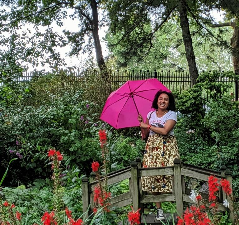 Woman laughing under an umbrella in a garden photo by LensMomentsNS 2019