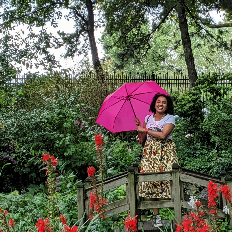 Woman laughing under an umbrella in a garden photo by LensMomentsNS 2019