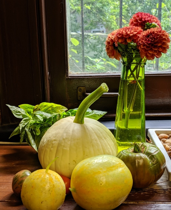 still life showing freshly picked late summer produce, cucumber, tomato, basil, gourd, zinnia